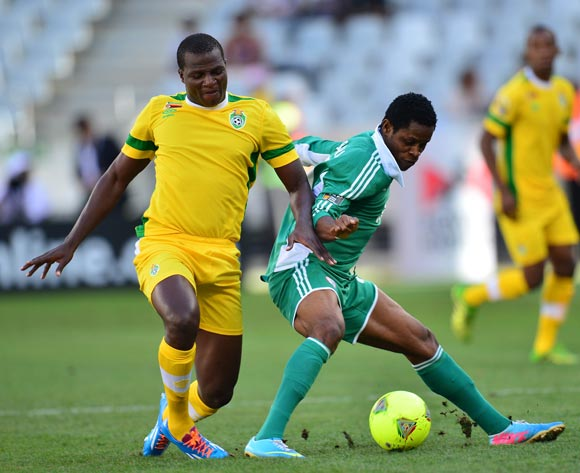 Dumte Pyagbara of Nigeria shields ball from Oscar Machapa of Zimbabwe during the 2014 CAF African Nations Championships 3rd/4th playoff between Zimbabwe and Nigeria at Cape Town Stadium, Cape Town on 1 February 2014