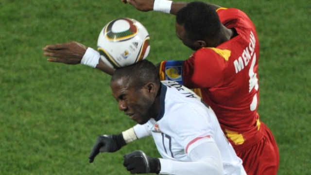 US striker Jozy Altidore (L) fights for