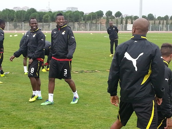 Asamoah Gyan and Agyemang-Badu walk on as they pass a comment to Andre Ayew