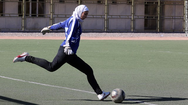 Female footballer playing with headscarf