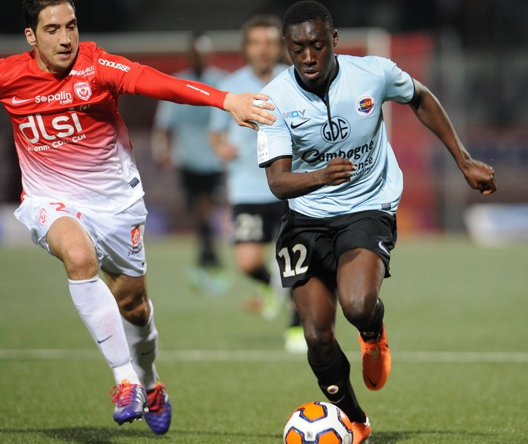 Dennis Appiah, right with the ball, has helped his loan club Caen to secure promotion to the French Ligue 1