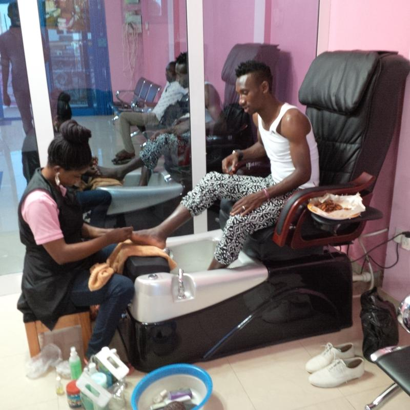 Harrison Afful receiving treatment at her wife's beauty parlour.