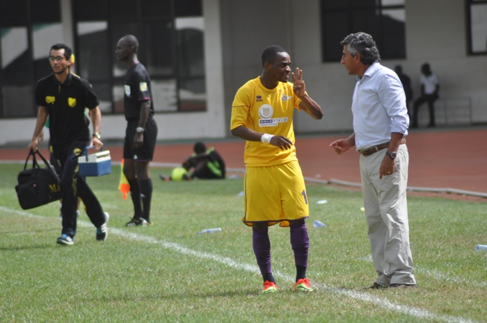 Michael Helegbe speaking to his coach Carlos Roberto Paulette on the touchline.