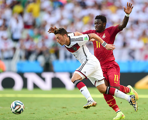 Germany's Mesut Ozil evades the challenge by Ghana's Sulley Muntari (right)