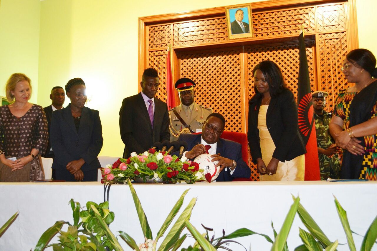 Ghana captain Asamoah Gyan watching on as President Peter Mutharika signs the Protect the Goal ball