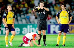 Matthew McKay of the Roar sits on the ground injured as referee Matthew Breeze indicates a substitution during the round 19 A-League match between the Central Coast Mariners and the Queensland Roar at Bluetongue Stadium.