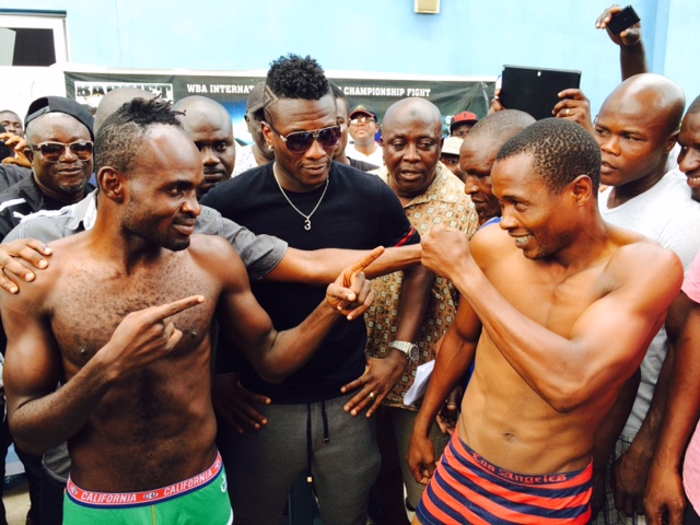 Tagoe faces off with Momba at the weigh-in session as Asamoah Gyan watches on