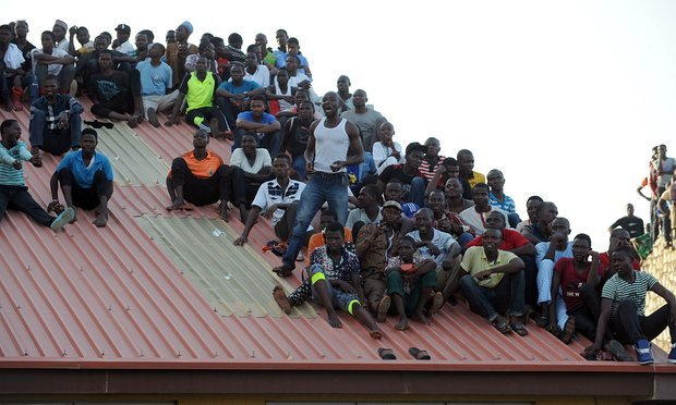Supporters sit on the roof of a house to watch the African Cup of Nations qualification match between Egypt and Nigeria.