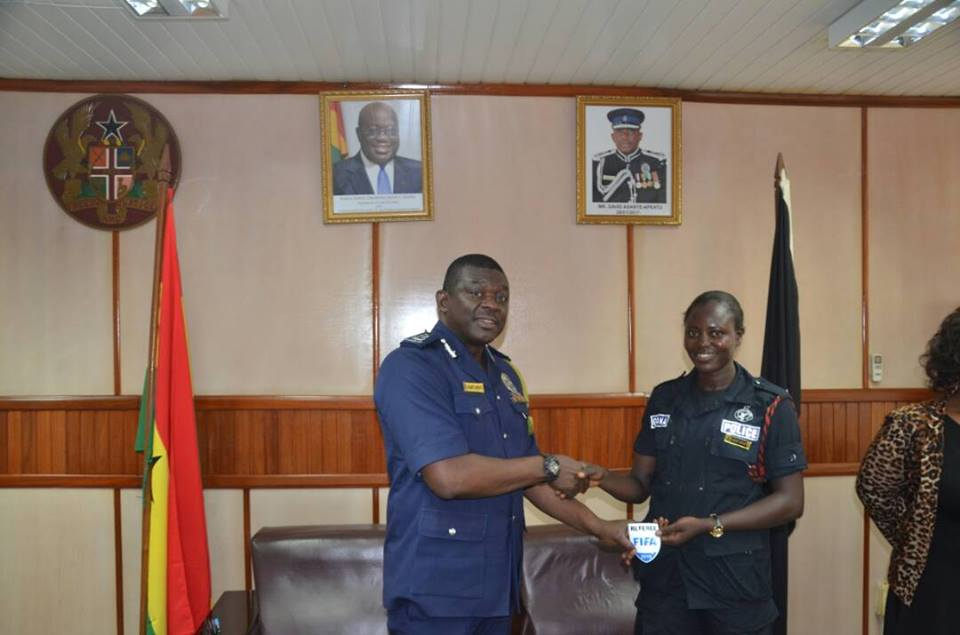 Referee Juliet Appiah represents FIFA badge to Inspector General of Police
