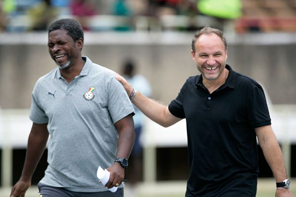 Harambee Stars coach Sebastien Migne (right) shares a light moment with a member of the Ghanaian technical bench during their 2019 Africa Cup of Nations Group