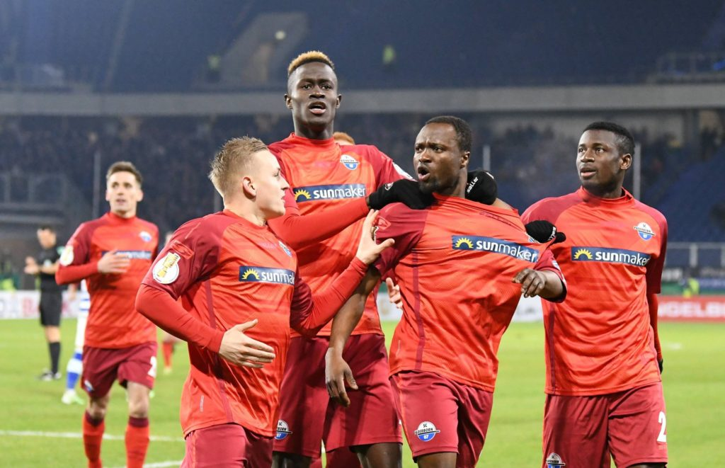 Bernard Tekpetey celebrates with team mates after scoring in the match